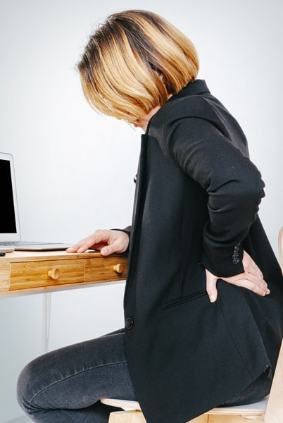 Officer worker with lower back pain sitting at her desk