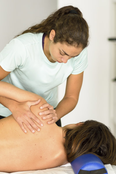 Physio (physiotherapist) gently treating woman with shoulder pain in a clinic