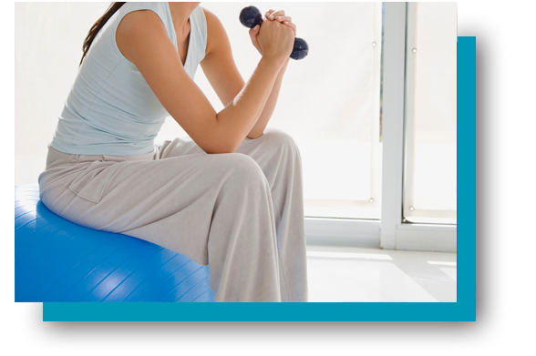 Woman exercising with dumbbell and ball